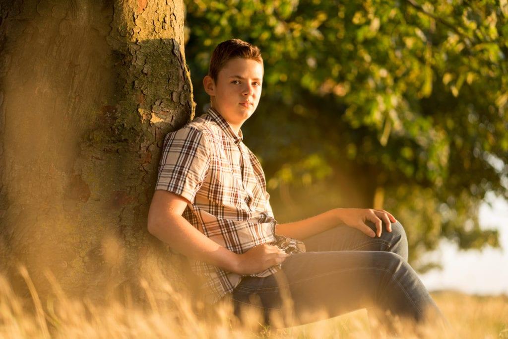 summer sun boy posing by tree